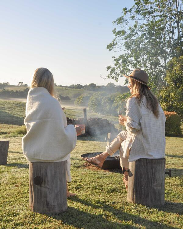 two women drinking tea in the early morning by a fire sitting on tree stumps looking over lush green hills in the byron bay hinterland