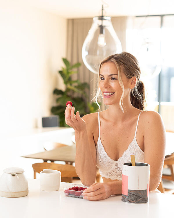 woman eating raspberries at kitchen bench with tea and teapot sitting next to her