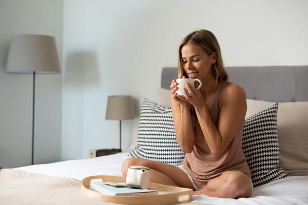 woman drinking tea and relaxing on bed with teapot and book