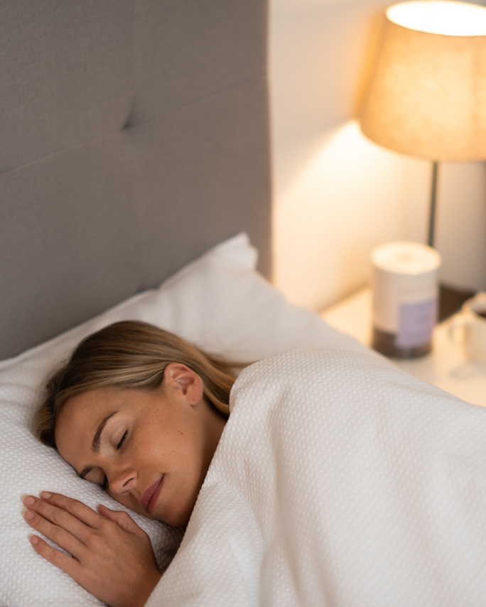 woman sleeping in bed with lamp on bedside table and tea